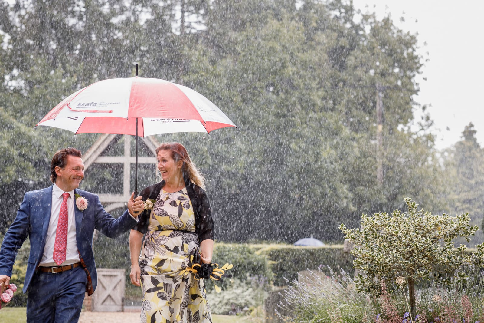 guests arriving to wedding in pouring rain with umbrella