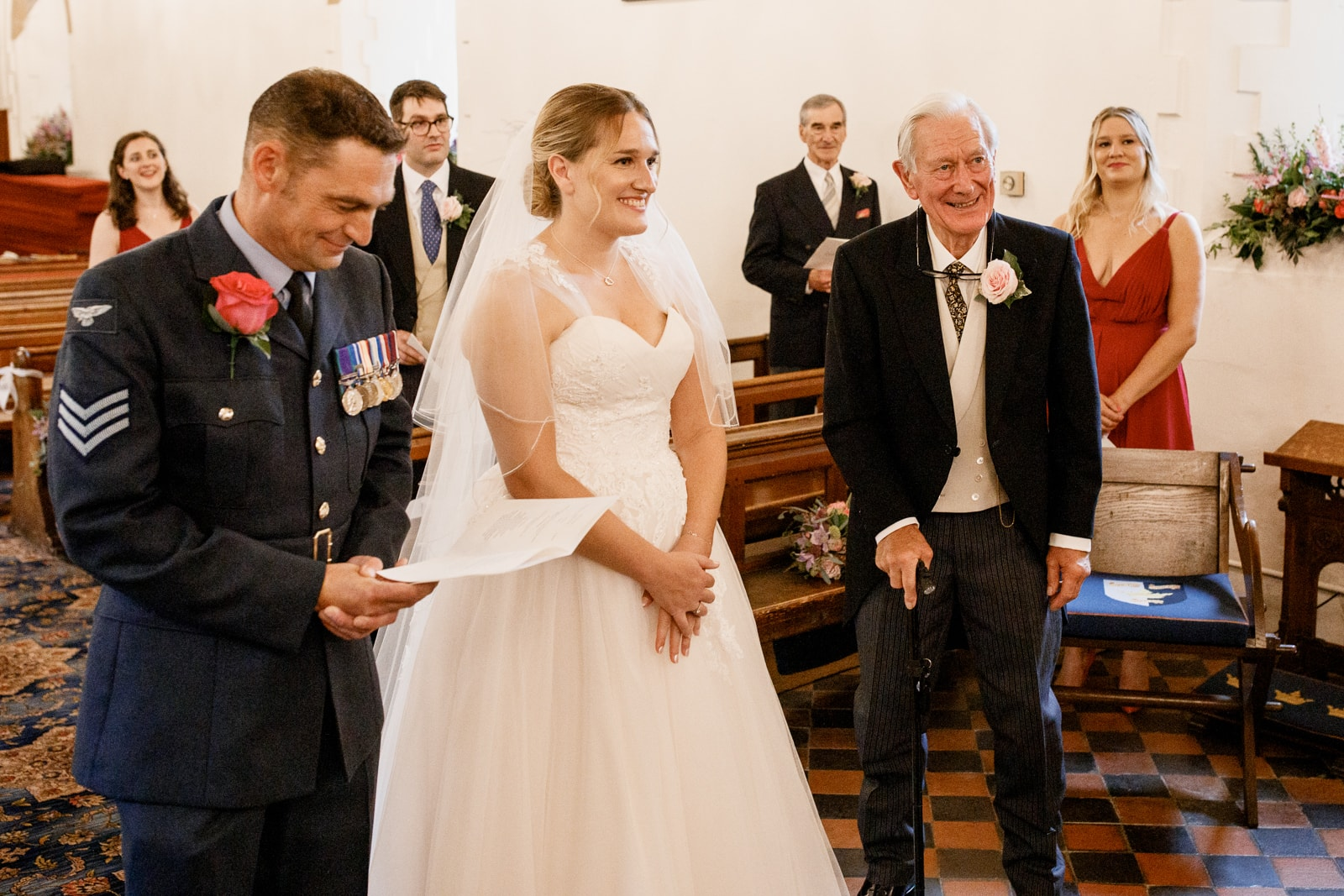 bride and groom at altar in church with father looking on