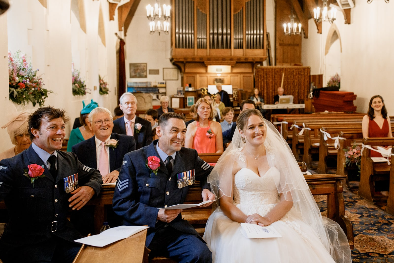 bride and groom laughing at all saints church in coleshill