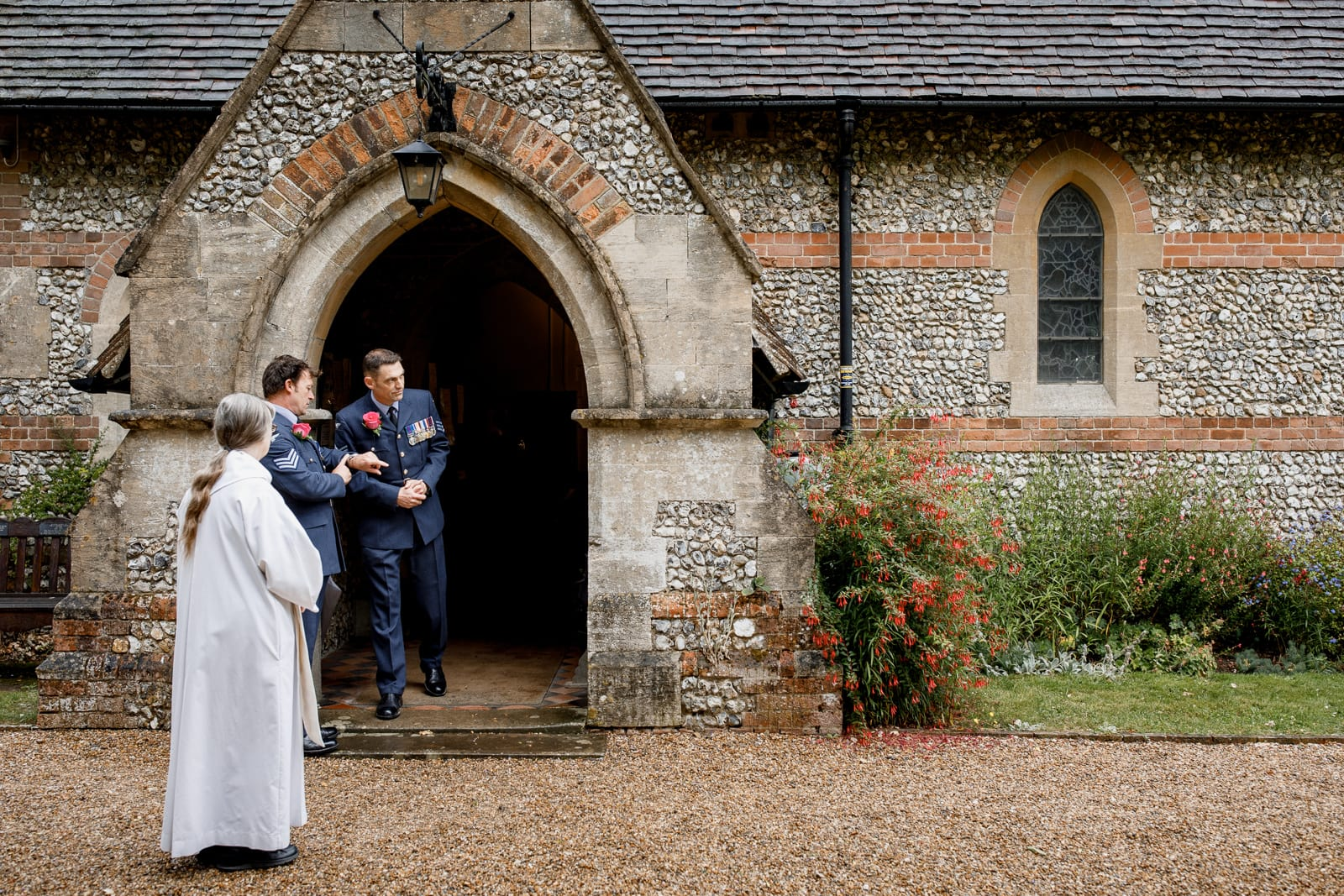 groom and best man outside all saints church wedding in coleshill