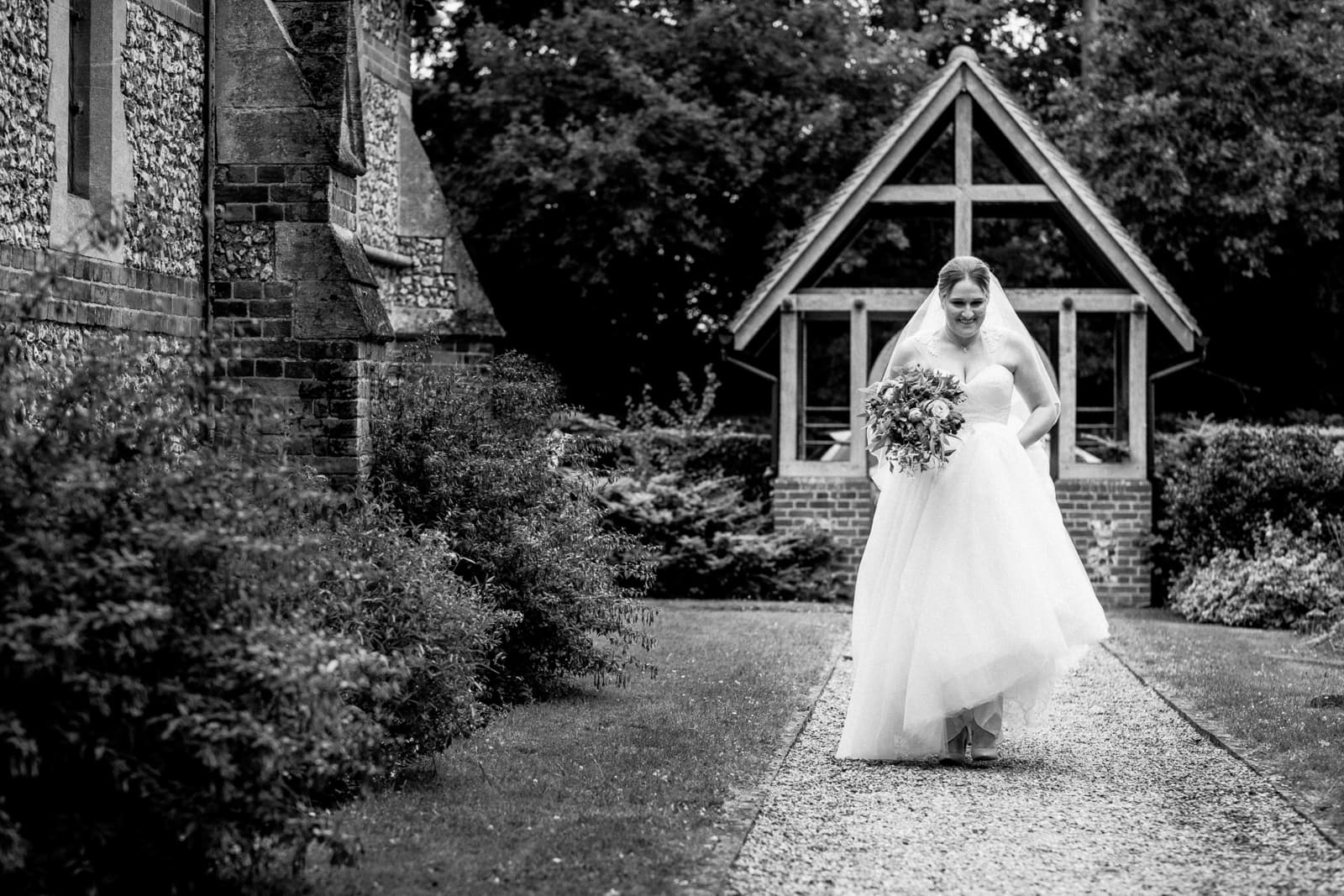 bride walking towards all saints church in coleshill for her wedding