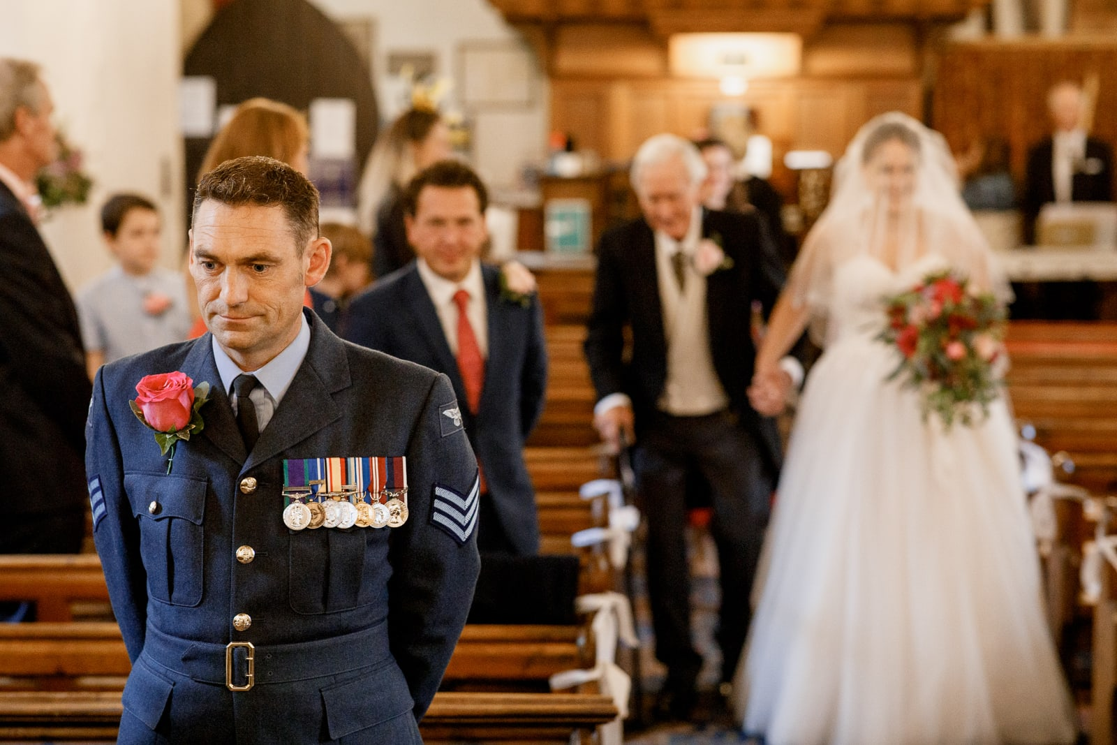 military groom waiting at front of church for bride arriving