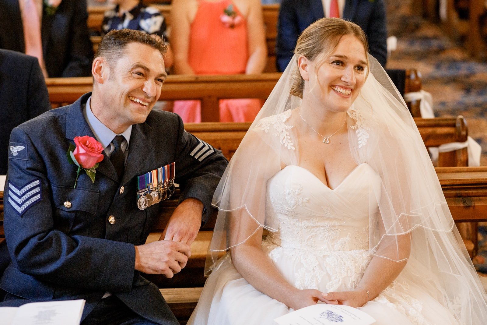 bride and groom smiling in church