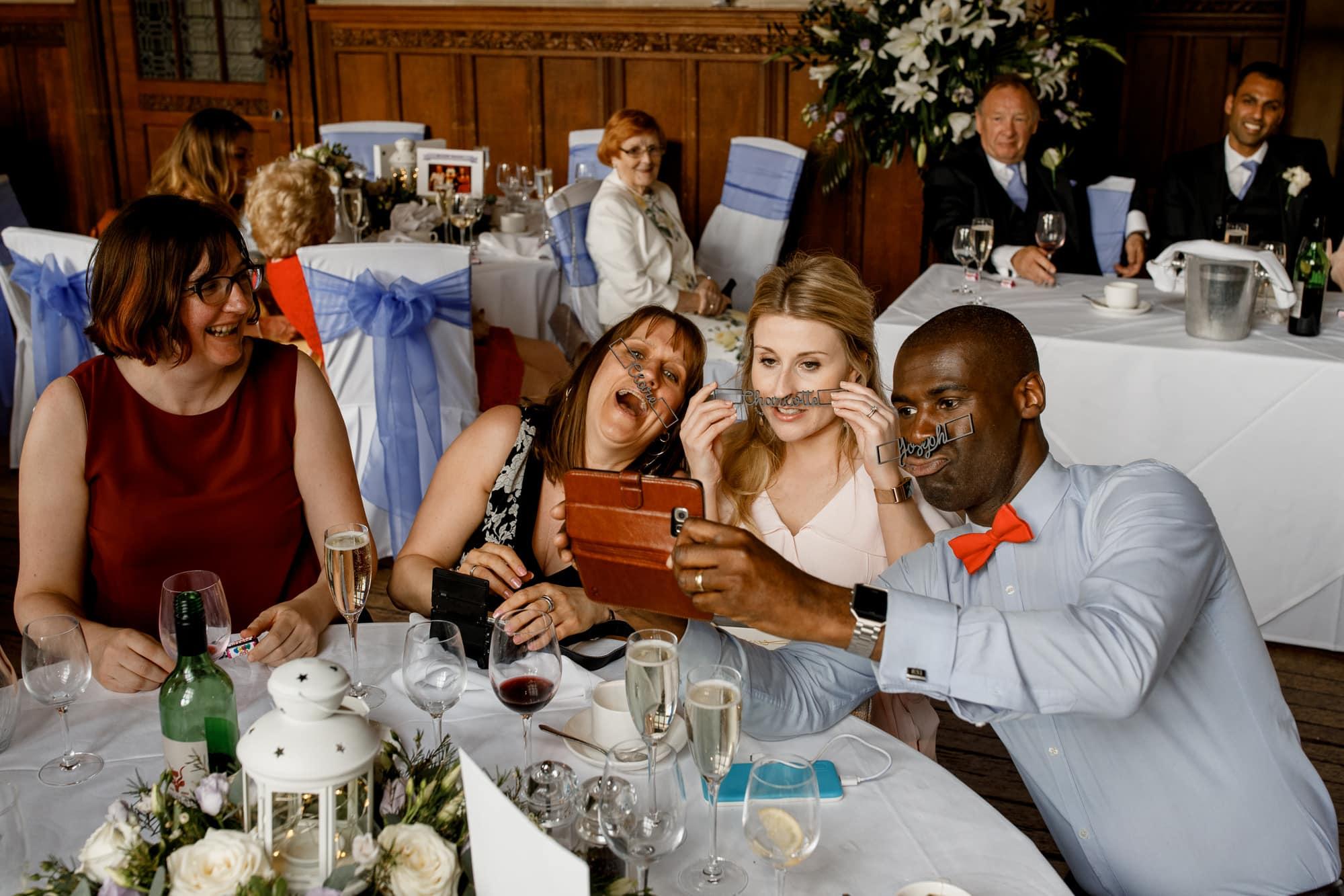 guests taking selfies at wedding