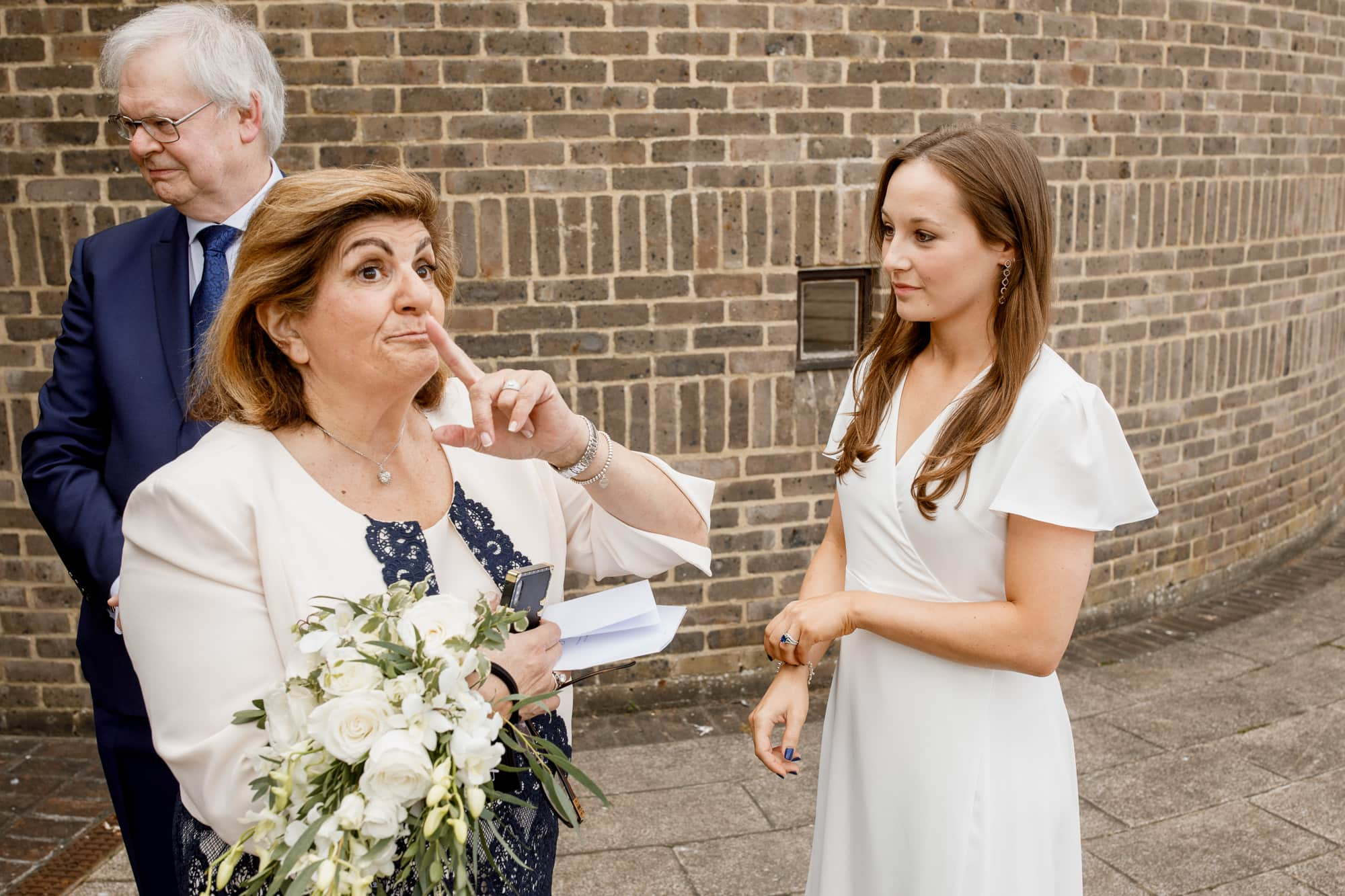 mother of the groom holding finger to lips