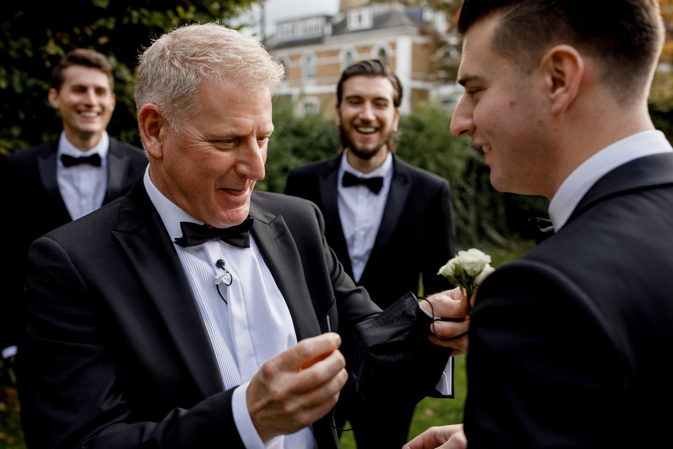 father of the groom pinning lapel flower